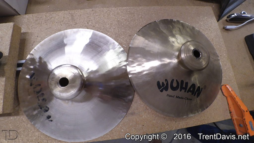 Fig. 15 - This is a shot of both cymbals. The one on the left is halfway through cleaning up the top. This was problematic due to the imbalance in that cymbal which is caused by the mounting hole being so far off-center.