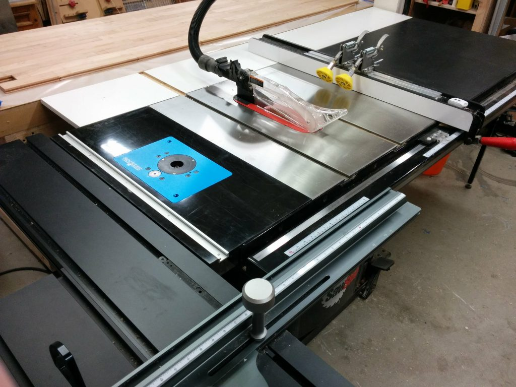 The sliding crosscut table mounted to a router table on the left of the saw.