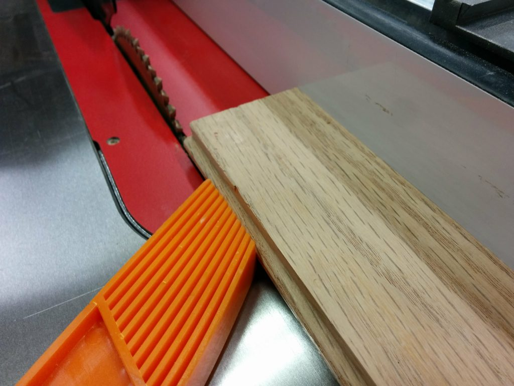 Cutting the tongue off several pieces of flooring.
