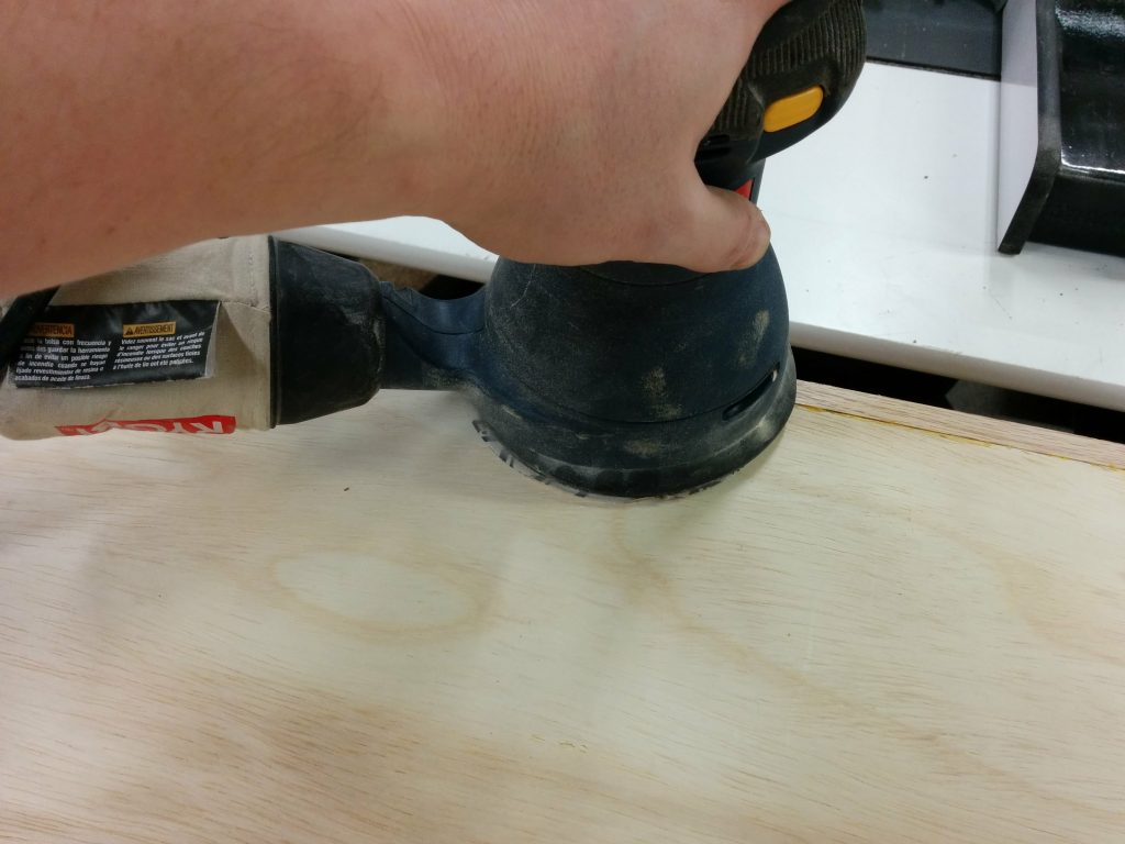 Sanding the bottom smooth to get rid of the glue squeeze-out.