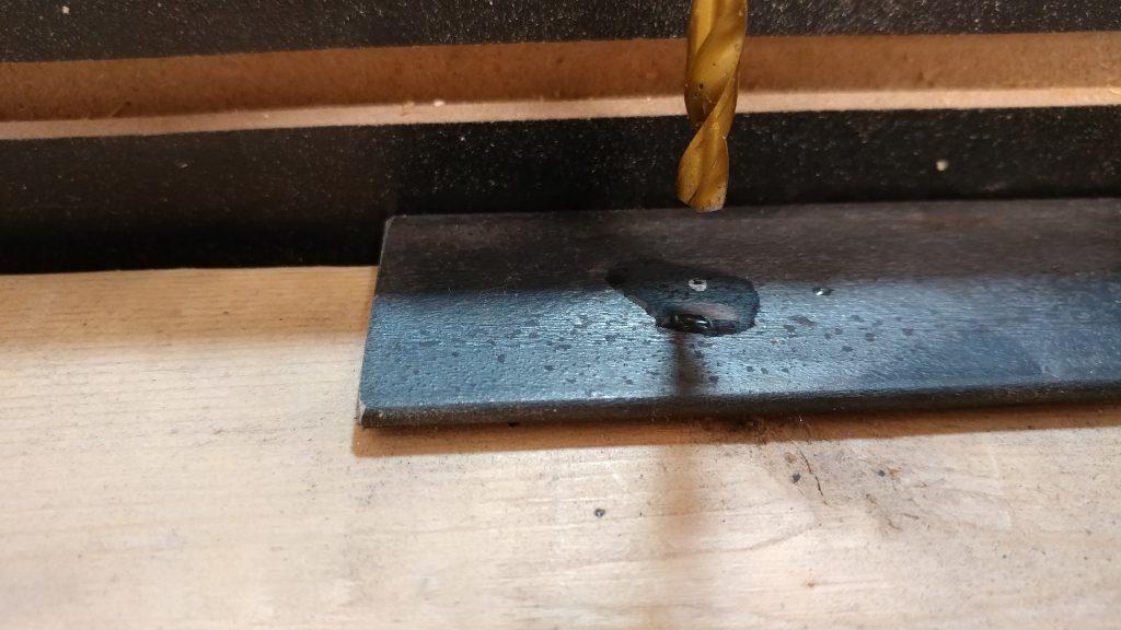 I applied a few drops of 3-in-1 oil to the steel before drilling.