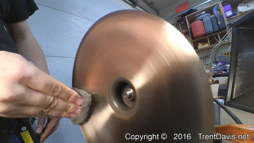 Fig. 6 - Finishing up the underside of the first cymbal with some 0000 steel wool.