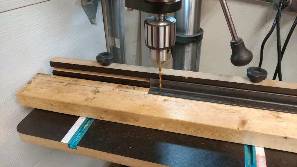 Setting up the drill press for drilling through the angle iron.