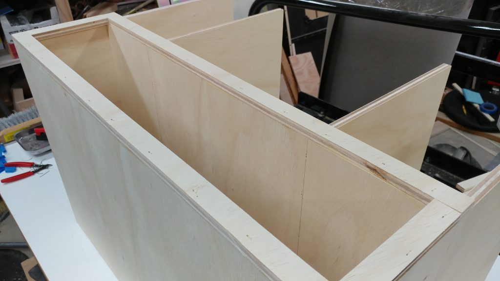 The framing for the bottom drawer opening are glued and nailed in place.